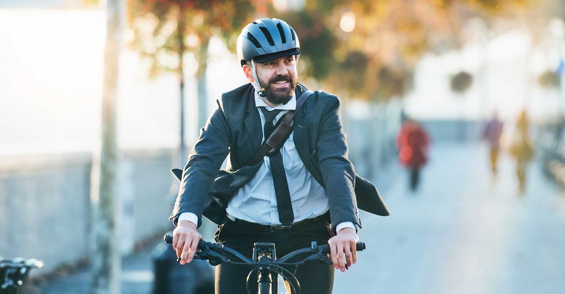 Hipster businessman commuter with electric bicycle traveling home from work in the city.