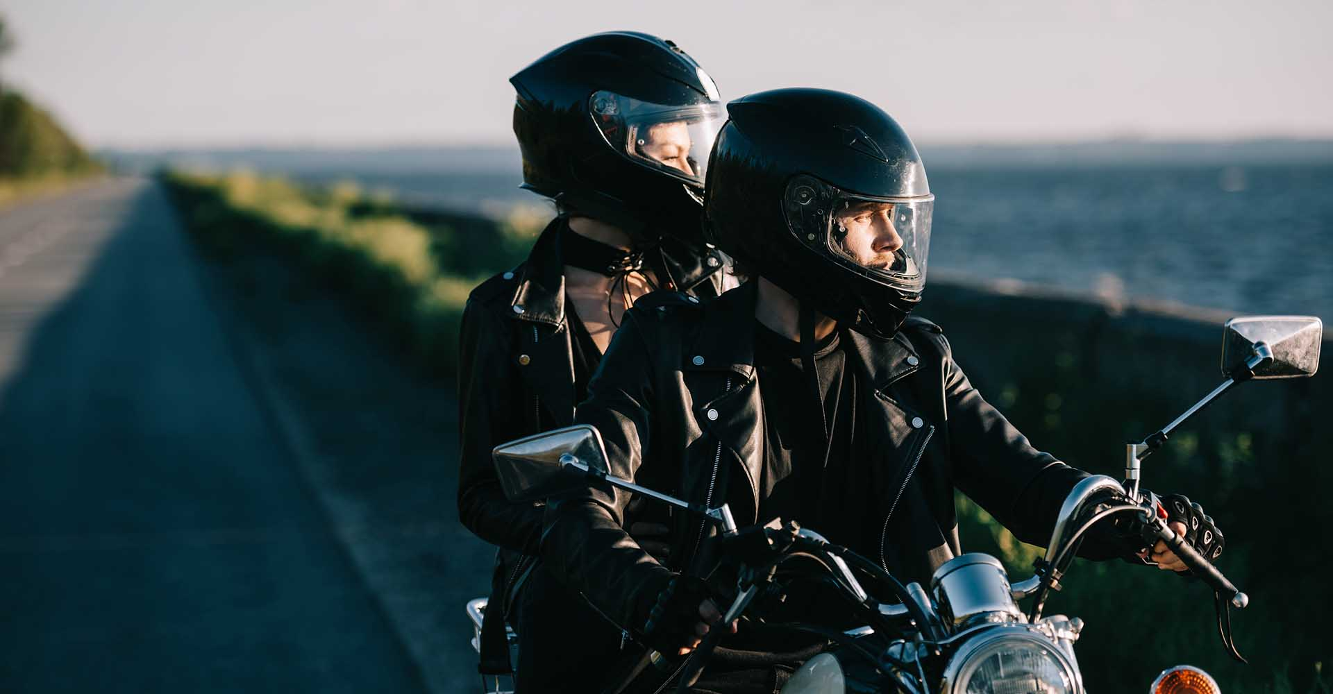 Couple of bikers in helmets riding classical motorcycle on country road.