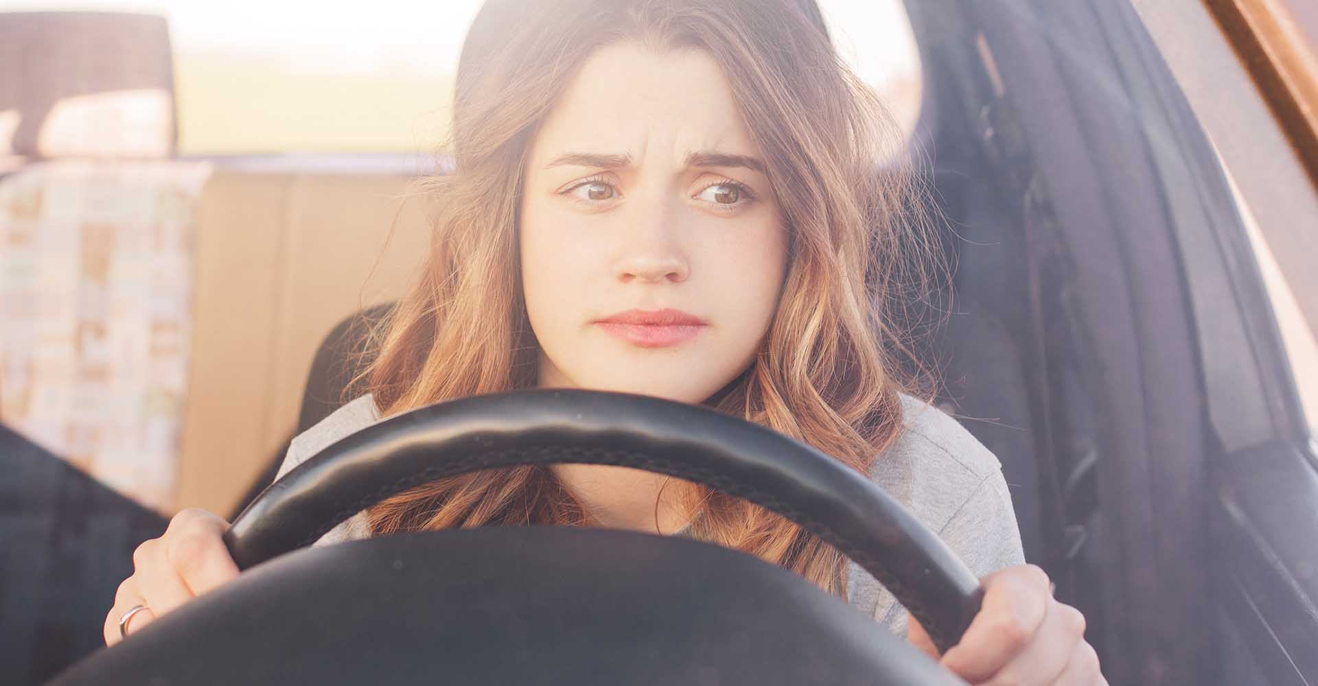 Nervous female driver sits at wheel.
