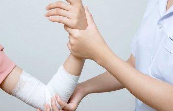 Nurse applying bandage to patient injured elbow.